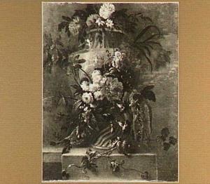 Stilleven van bloemen rondom een geornamenteerde tuinvaas op een balustrade