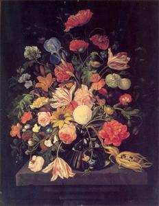 Bloemen in een glazen vaas op een stene console