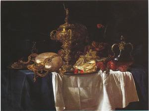 Pronkstilleven met siervaatwerk, vruchten en gevogelte op een blauw kleed met wit servet