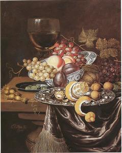 Vruchtenstilleven met roemer en vaatwerk op een deels met een laken bedekte tafel
