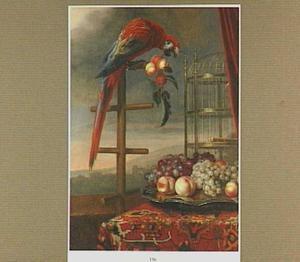 Stilleven van een Ara met een tak perziken in zijn bek, een vogelkooi en een schaal met vruchten; in de achtergrond een doorkijk naar een landschap