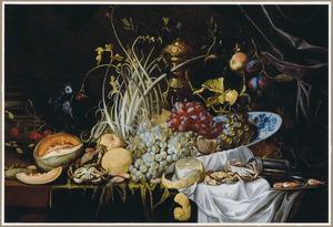Stilleven met vruchten, schaaldieren en siervaatwerk op een gedekte tafel