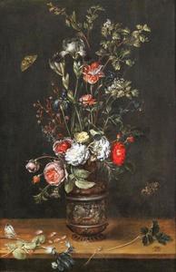 Bloemstilleven van rozen, irissen en een tulp in een geornamenteerd vaasje op een houten plint