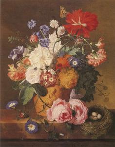 Bloemen in een terracotta pot en een vogelnest op een stenen plint