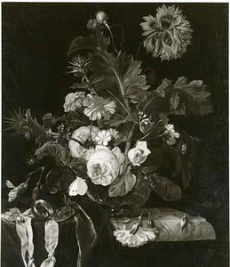 Bloemen in een glazen vaas op een deels gedekte tafel