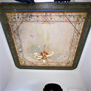 Plafond voorzien van een wolkenlucht omgeven door treillage van bamboe