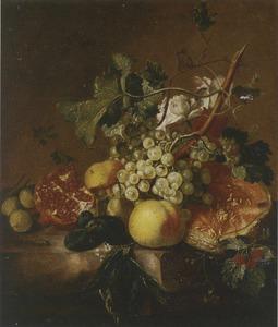 Een halve meloen, granaatappel en andere vruchten op een marmeren blad