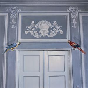Trompe l'oeil schildering met bovendeurstuk en twee papegaaien