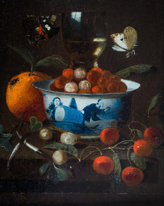 Een porseleinen kom aardbeien op een stenen blad, een roemer, vruchten en vlinders