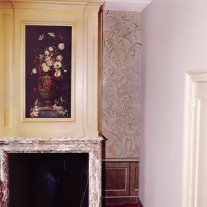 Wandschildering met arabeskenmotief terzijde van een schoorsteenbetimmering