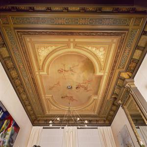 Plafond waarvan het middendeel beschilderd is met zwevende putti omgeven door ornamenten
