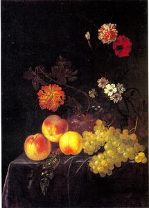 Perziken en druiven met anjers en andere bloemen in een glazen vaas op een beklede tafelrand